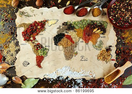 Map of world made from different kinds of spices on wooden background