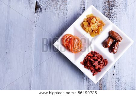 Dried fruits in white plate on color wooden table background