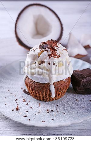 Delicious coconut cupcake with cream and chocolate chips on color wooden table background