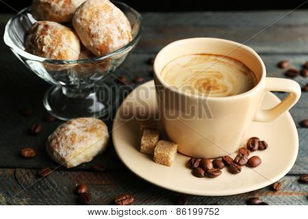 Cup of coffee and tasty cookies  on wooden table, on dark background