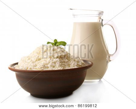 Glass jug of milk and clay bowl of cottage cheese isolated on white