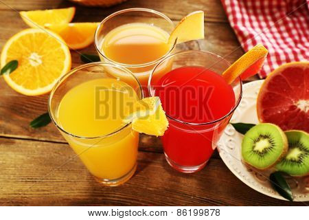 Fresh juices with fruits on wooden table