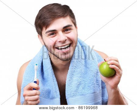 Portrait of smiling young man with toothbrush and green apple isolated on white