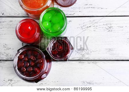Homemade jars of fruits jam on color wooden planks background