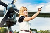 pic of propeller plane  - beautiful woman holding paper plane against real plane - JPG