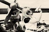 stock photo of propeller plane  - beautiful woman holding paper plane against real plane - JPG