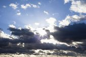 picture of sun god  - Cloudscape with the sun rays radiating from behind the clouds - JPG