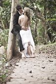 stock photo of flirt  - Young happy couple flirting outdoors along path in forest