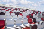 picture of tribunal  - Colorful empty plastic seats on new modern concrete stadium tribune - JPG