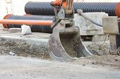 image of heavy equipment operator  - Excavator bucket digging ground for installing pipes at the street - JPG