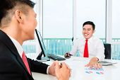 pic of asset  - Asian banker offering client finance assets in bank office  - JPG