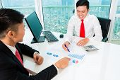 stock photo of asset  - Asian banker offering client finance assets in bank office  - JPG