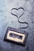 pic of magnetic tape  - audio cassette with magnetic tape in shape of heart on grunge background - JPG