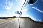 picture of reflection  - Blue sky with clouds and asphalt road reflected in side of car - JPG