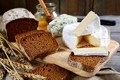 stock photo of brie cheese  - Brie cheese black bread slices roquefort and honey on a cutting board - JPG