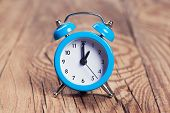 stock photo of analog clock  - blue alarm clock on a wooden table - JPG