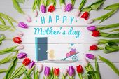 pic of wheelbarrow  - Chick with wheelbarrow of hearts against tulips on table - JPG