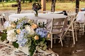 picture of wedding table decor  - Beautiful colorful wedding decorations of flowers on white tables in a garden - JPG