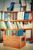 pic of wooden crate  - Books in wooden crate on bookshelves background - JPG