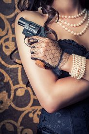 stock photo of girls guns  - woman wearing black corset and pearls and holding a gun against retro background - JPG