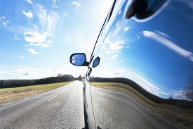 stock photo of reflections  - Blue sky with clouds and asphalt road reflected in side of car - JPG