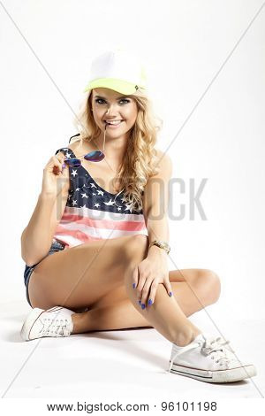 Portrait of a pretty blonde young adult beauty woman posing in American flag shirt and baseball cap and sunglasses isolated on white background