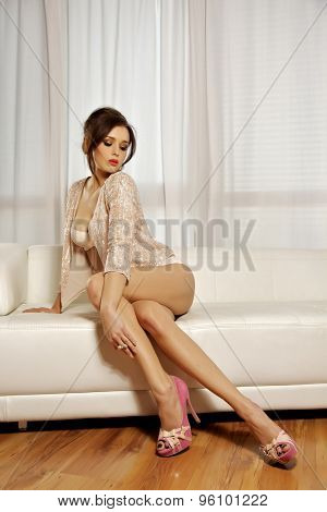 Portrait of a beautiful sensuality sexy and attractive young adult pretty brunette woman long legs on the white couch in luxury style apartment