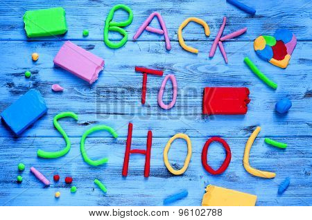 the sentence back to school written with modelling clay of different colors on a blue rustic wooden background