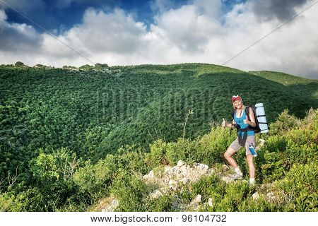 Traveler girl in the mountains, standing on the top of mount and showing by hands a good mood, active summer time, with interest discovering wild nature