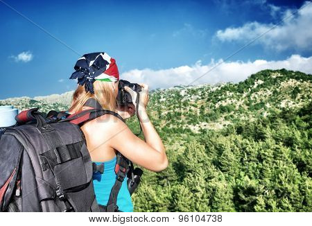 Young woman photographing beautiful mountains landscape, active backpacker girl enjoying amazing view on wild nature through the lens of her camera