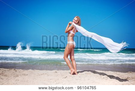Beautiful woman on the beach, sexy slim model walking along sandy coast with white scarf fluttering in the wind, happy summer vacation