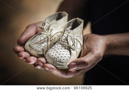 Man holding old and worn leather baby shoes in his hands.