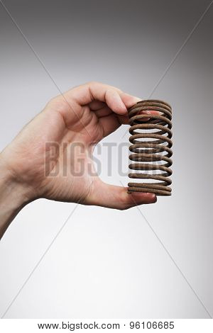 Man holding an old rusty spring is his hand.