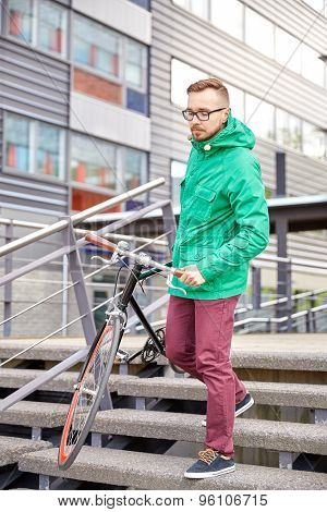 people, sport, style, leisure and lifestyle - young hipster man carrying fixed gear bike down stairs in city