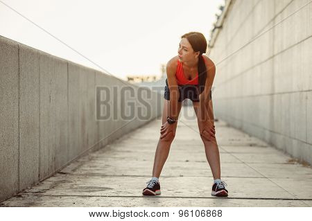 Young caucasian woman taking breath after jogging