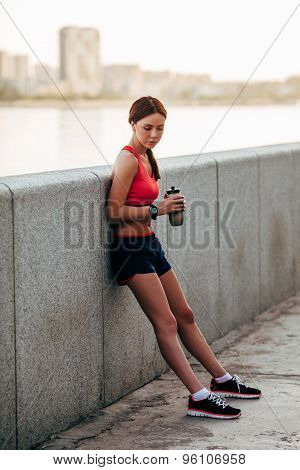 Female runner with bottled water tired