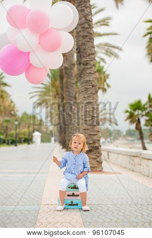 Happy little girl sitting on a pile of colorful small suitcases, holding a bunch of pink and white party balloons on a sidewalk with tropical palm trees