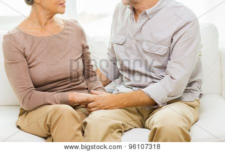 family, relations, age and people concept - close up of happy senior couple holding hands on sofa at home