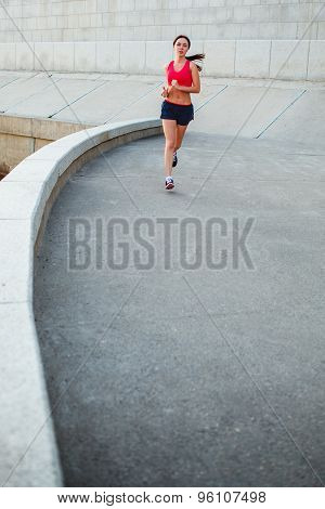 woman runnning along granite curved parapet