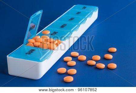 Orange pills in weekly dispenser