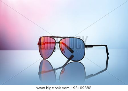 Sunglasses on reflective surface.