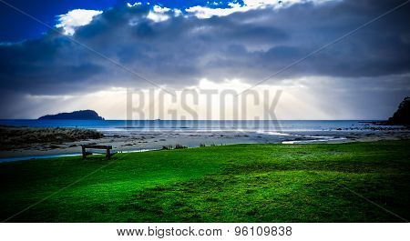 Whangamata Beach. Bench With View Over The Beach Into The Cloudy Sky At Sunset. Sunbeams Are Visible