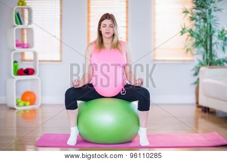Pregnant woman doing yoga on exercise ball in the living room