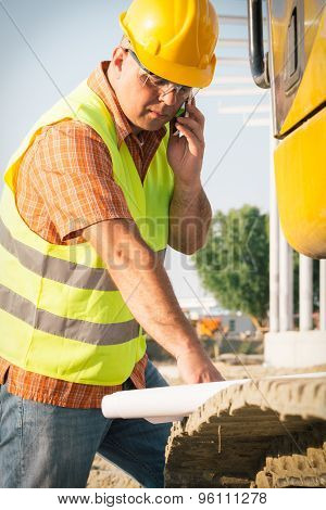 Construction manager controlling building site with plan