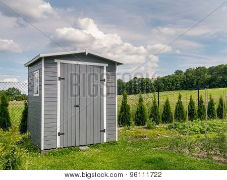 Wooden garden tools shed painted in gray color
