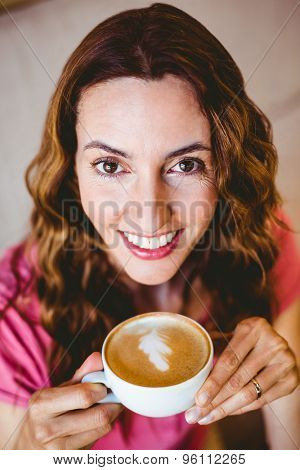 Pretty brunette having cup of coffee at the cafe