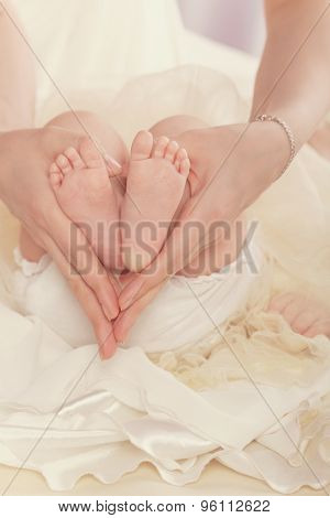 Mother Holds Feet Of Her Child.
