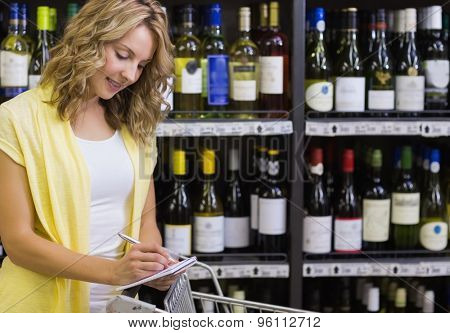 Smiling blonde woman writing on her notepad in supermarket
