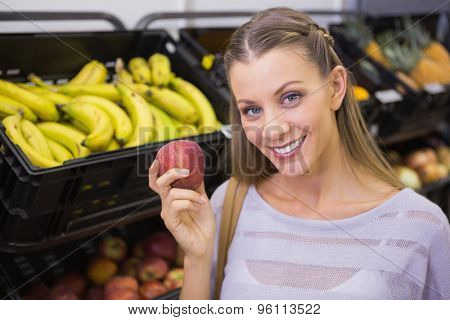 Smiling pretty blonde woman showing a red apple