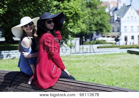 Two Stylish Ladies Leaned On A Bench